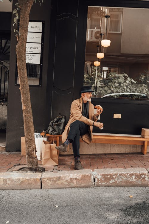 Elderly man sitting on bench and drinking hot beverage