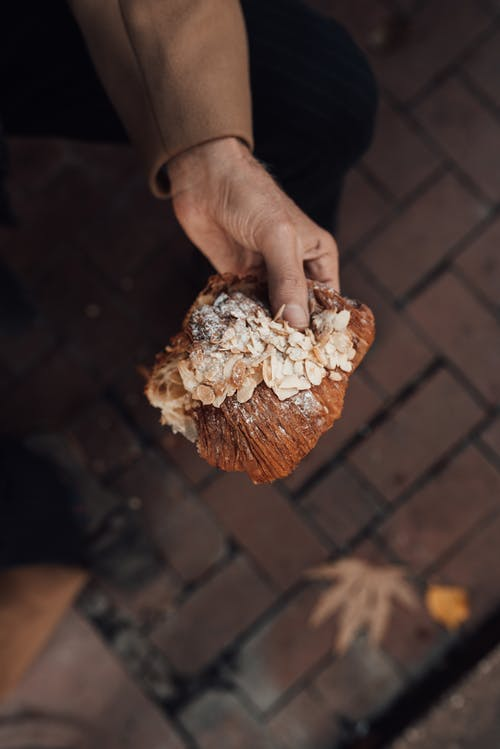 Hand holding delicious croissant with nuts