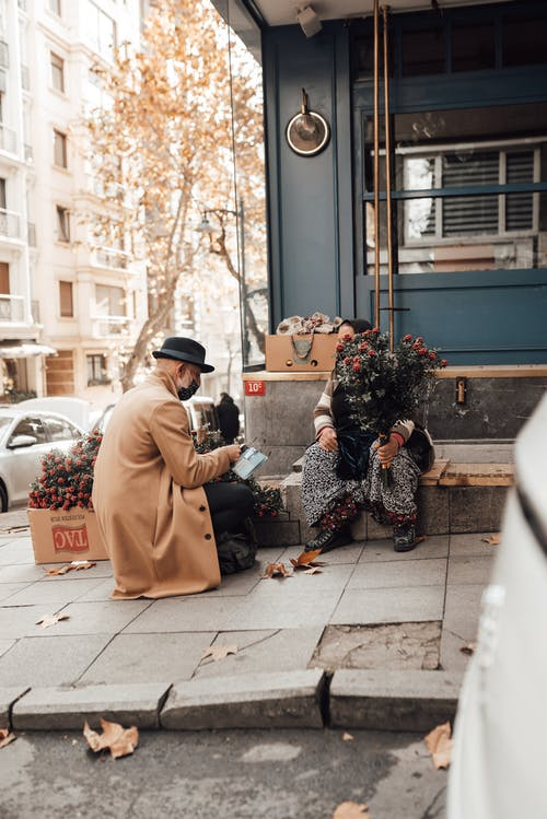 Full body of unrecognizable female selling flowers to man while sitting on bench on sidewalk near building on street in city