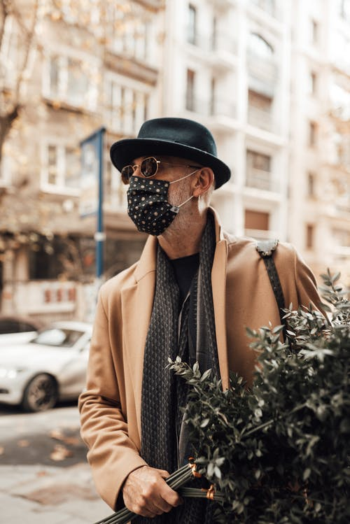 Stylish man in protective mask with bunch of branches