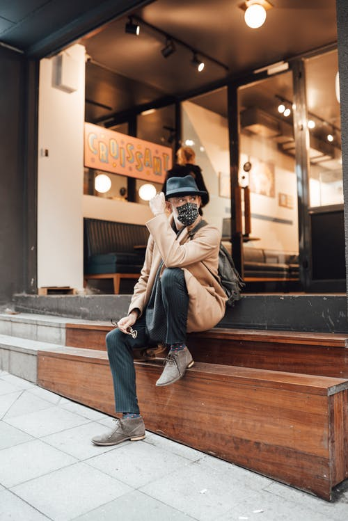 Stylish man in mask sitting on steps