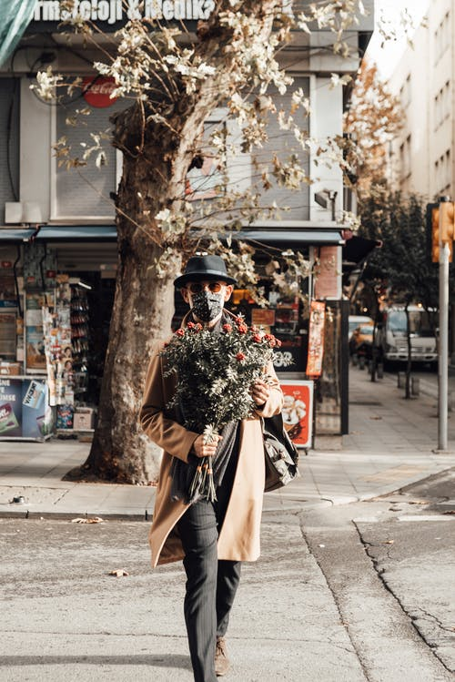 Stylish man with backpack and bouquet strolling on road