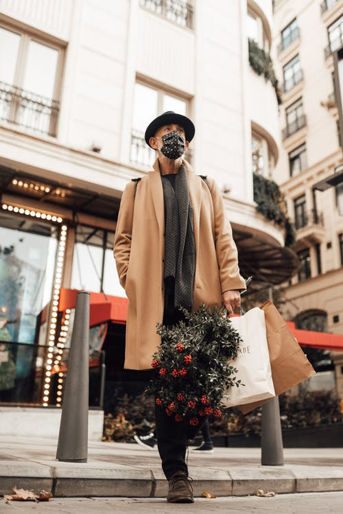 Stylish man with shopping bags and bouquet on sidewalk