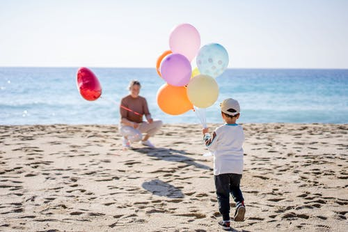 Boy in White Long Sleeve Shirt and Black Pants Holding Balloons on Beach