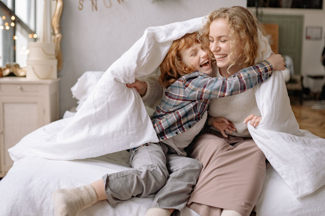 A Mother and Daughter Smiling while Under a Blanket