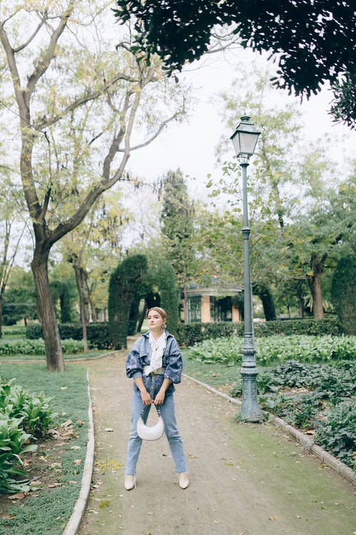 Woman in White Shirt and Black Pants Standing on Pathway Near Green Trees