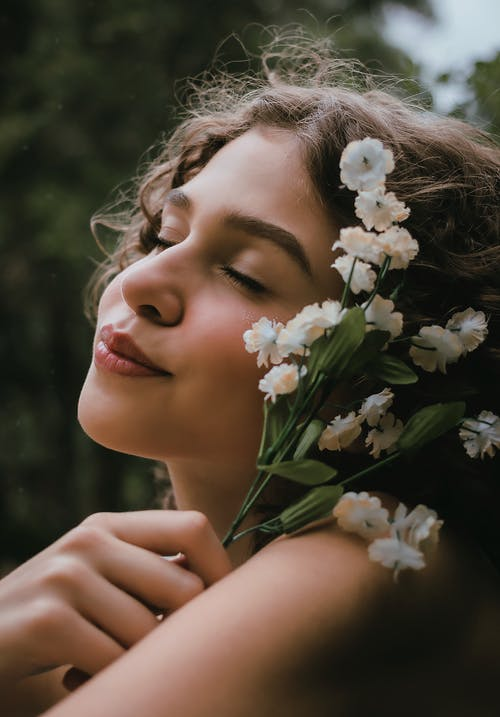 Woman with flower near face with closed eyes in nature