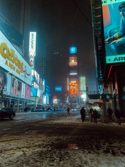 Anonymous pedestrians on snowy sidewalk and road with cars near buildings with glowing signboards in city street at night in winter