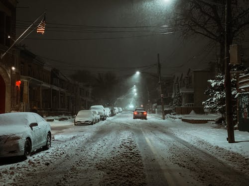 Snowy road with cars near building in evening in town