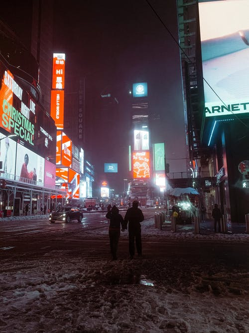 Anonymous people on snowy road near glowing buildings and walkway