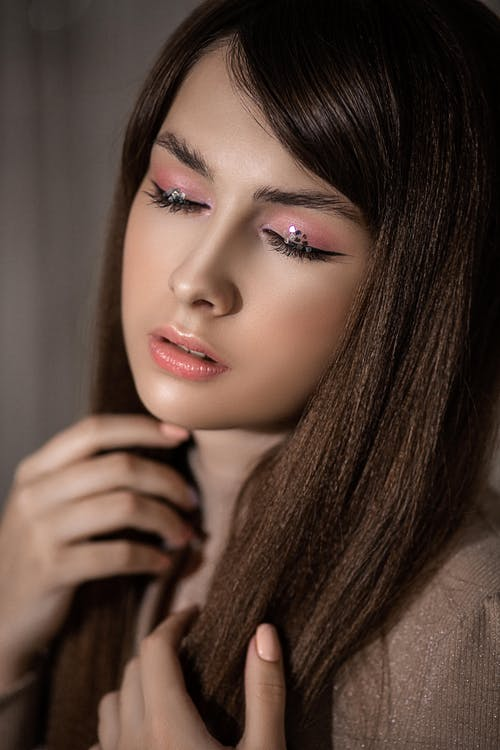 Crop young mindful gentle female with makeup and glitter on eyeshadow touching hair in daytime