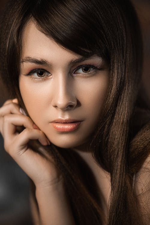 Crop young tender female with delicate skin and sincere gaze touching face while looking at camera
