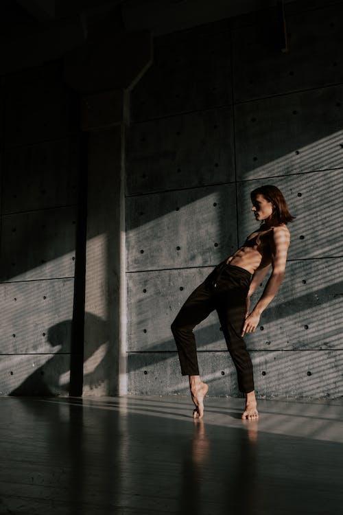 灰色のコンクリートの床の上を歩く黒いタンクトップと黒いズボンの女性