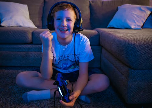 A Happy Boy Playing Video Games while Sitting on the Floor