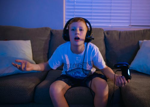 A Boy Playing Video Games while Sitting on a Sofa