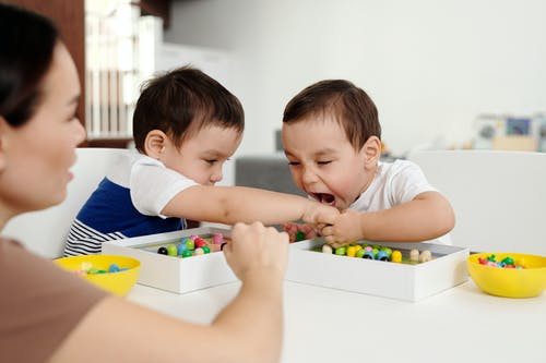 One Little Boy Trying to Bite Other One While Playing