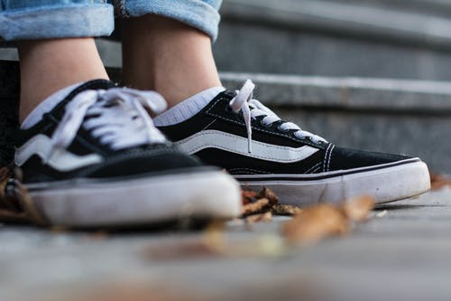 Close-Up Shot of a Person Wearing Black Vans Sneakers