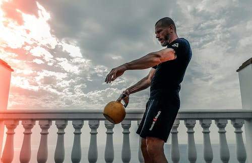 Man in Black Shirt Carrying Kettle Bell Outdoors