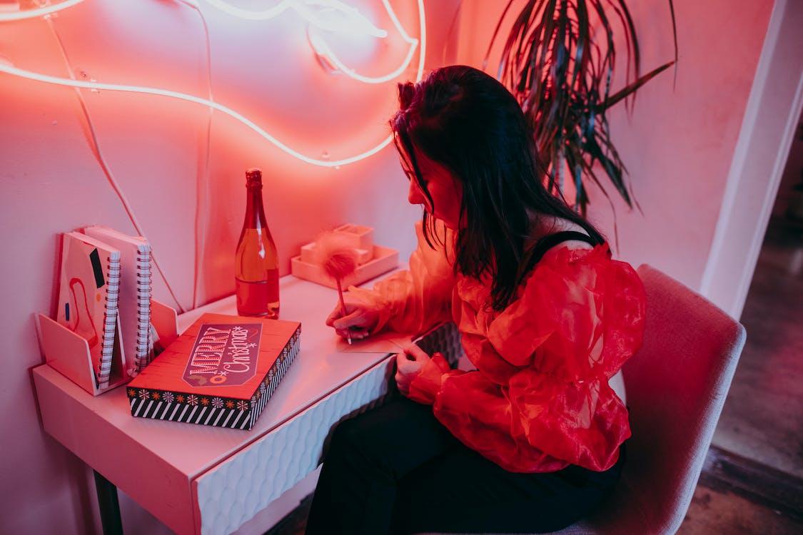 Donna In Camicia A Maniche Lunghe Rossa Che Si Siede Sulla Sedia