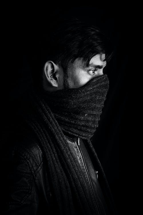 Black and white of serious male with scarf on face in leather jacket standing in dark room