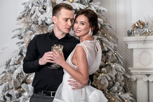 Loving couple with champagne glasses embracing near Christmas tree
