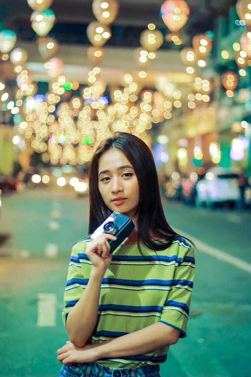 Young Asian woman with vintage photo camera on asphalt road