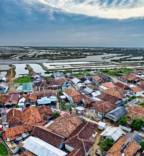 Small settlement with typical residential buildings with colorful roofs located in rural terrain near agricultural rice fields against cloudy sky