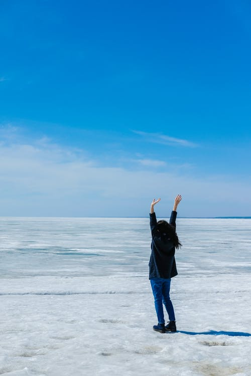 Back view full length of unrecognizable lady in casual outfit standing on endless icy terrain near frozen sea with raised hands under blue cloudless sky in daytime