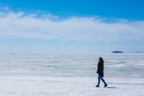 Faceless woman walking on icy coast near frozen ocean