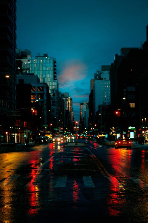 Asphalt road with crosswalk and glowing vehicles near buildings in twilight under blue cloudy sky in city district