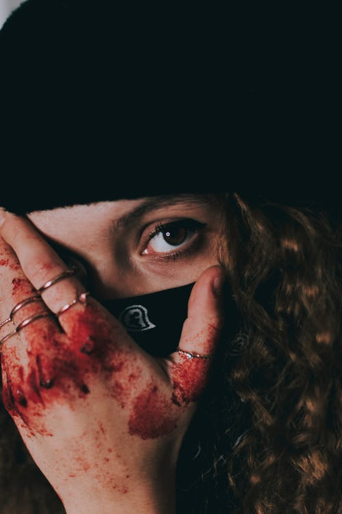 Unrecognizable female in black mask and hat covering face with hand in blood and looking at camera