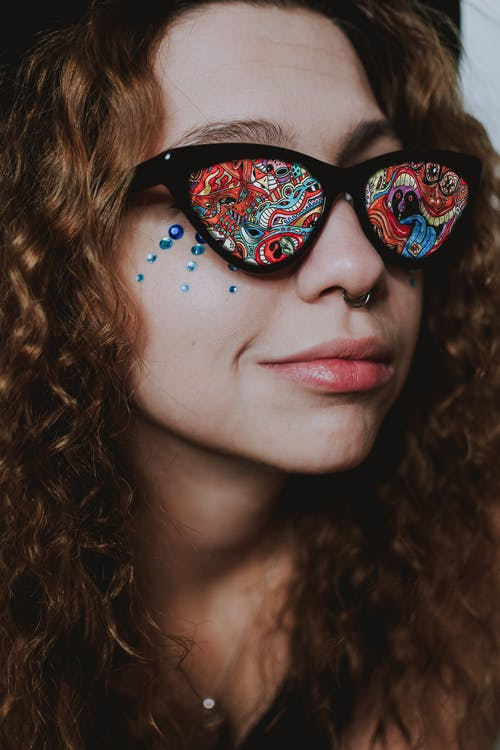 Closeup of cheerful young female in sunglasses with vivid multicolored lenses with ring in nose and rhinestones on face looking away
