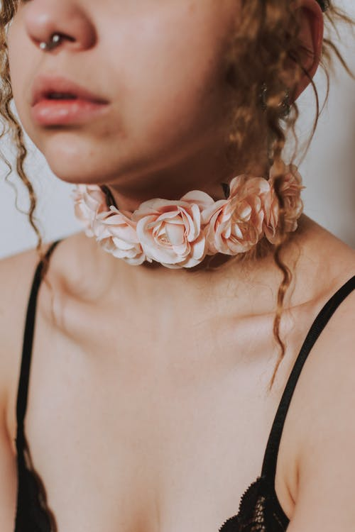 Closeup of crop anonymous female with piercing in nose and choker decorated with flowers in black bra