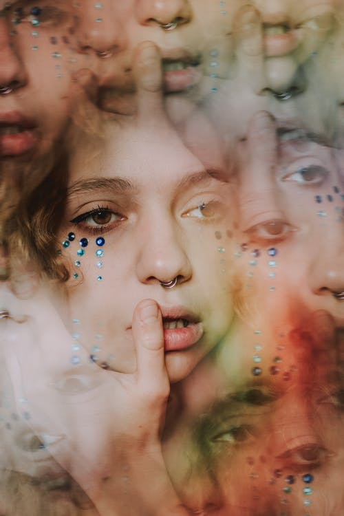 Abstract kaleidoscopic portrait of young lady with rhinestones on face and piercing in nose with makeup touching lips with finger and looking away thoughtfully