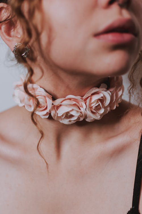 Crop anonymous female in pink flowers on choker with earring on white background in light place