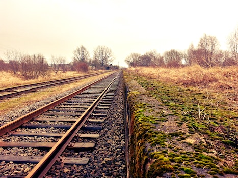 Railway Next to a Grassy Field during Day Time