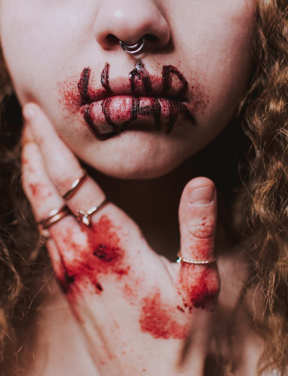 Crop anonymous female victim wearing rings and piercing in nose while touching cheek with hand with blood and wounds on knuckles and word liar written with marker on bloody lips