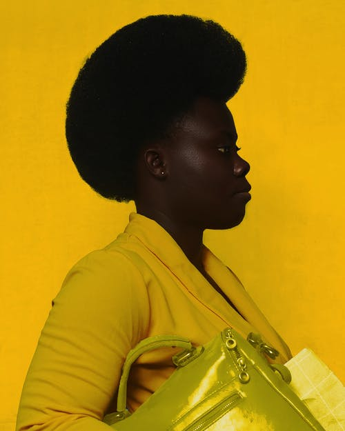 Side view of African American female with yellow bag  wearing trendy yellow dress and looking away