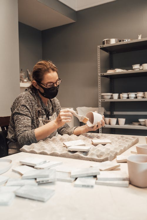 Lady in casual outfit and glasses in protective mask painting clayware with paintbrush near tile pieces on soft uneven mat on table near shelves with utensil in light studio