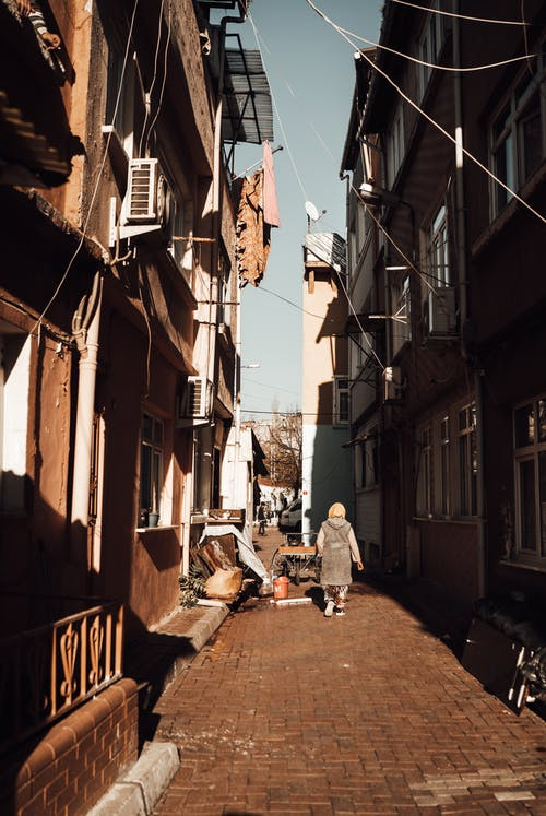 Narrow city street with houses and anonymous woman in daytime
