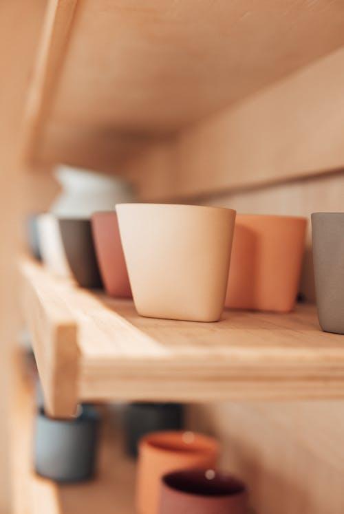 Set of various ceramic pots on shelves in workshop