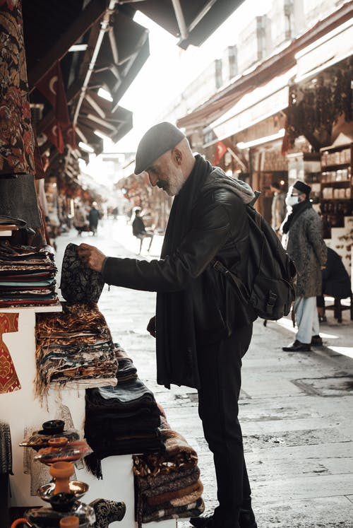 Side view of unrecognizable mature man in casual clothes and hat with backpack standing on market near street stall with fabric near people in daytime in city
