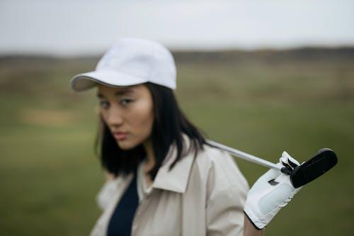 Wanita Bertopi Putih Dengan Klub Golf