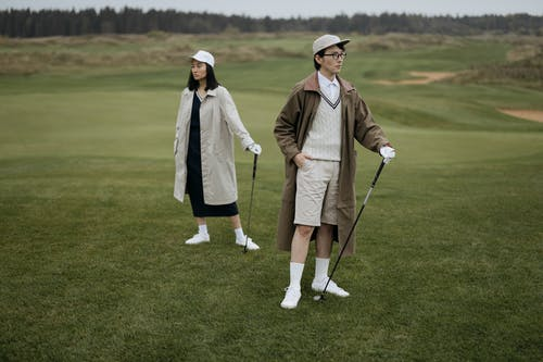 Man and Woman with Golf Clubs on Golf Course