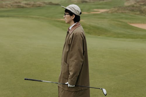 Man in Brown Coat and Black Cap Holding Golf Club