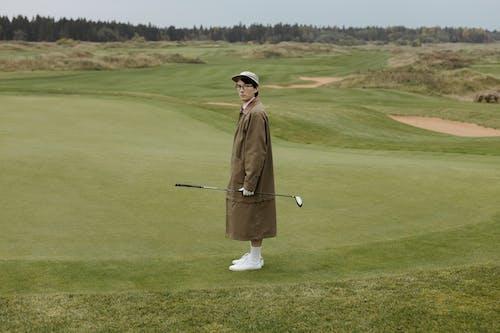 Man in Brown Robe Holding Golf Club on Green Grass Field