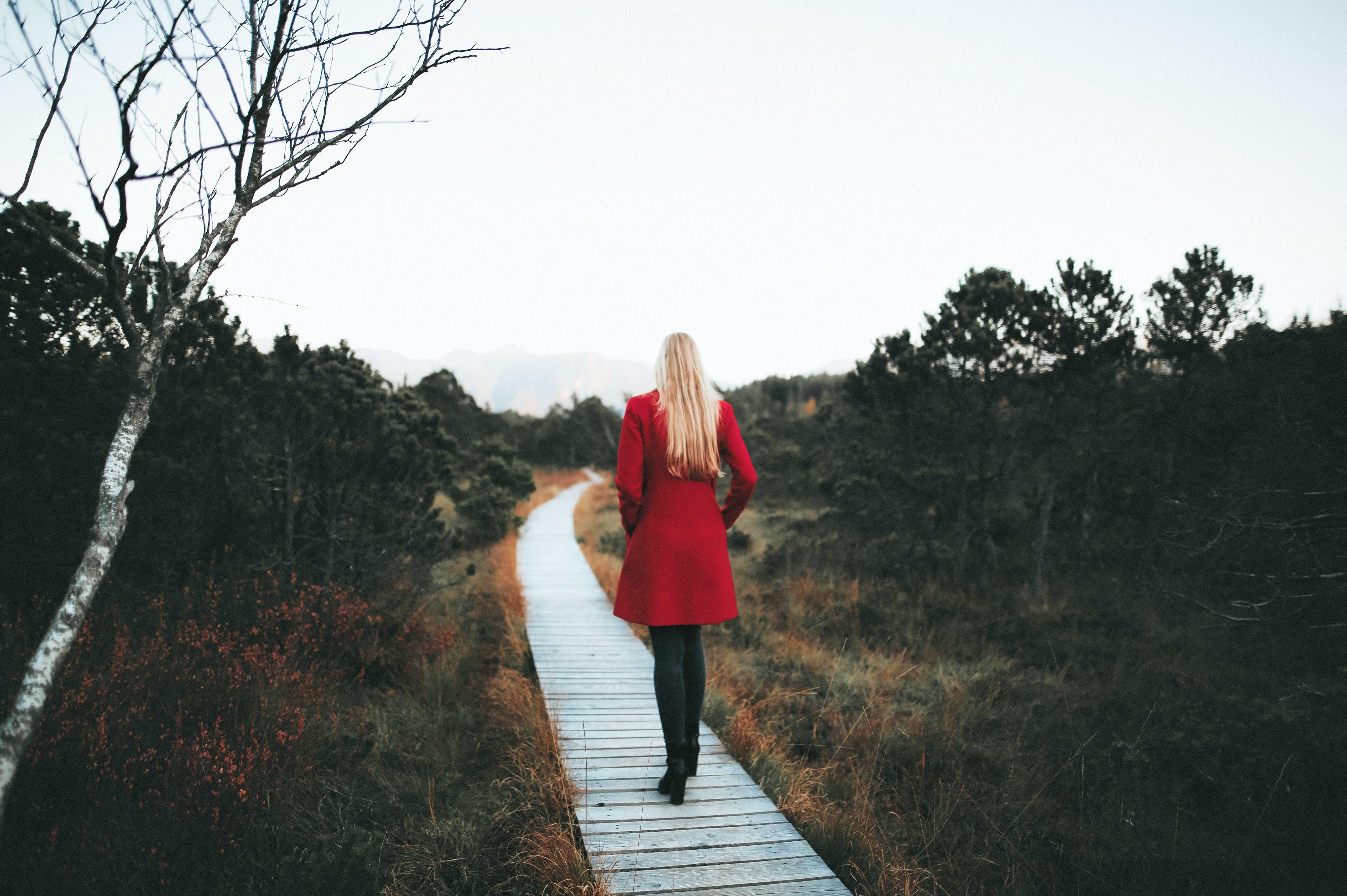 Woman Walking on Wooden Pathway