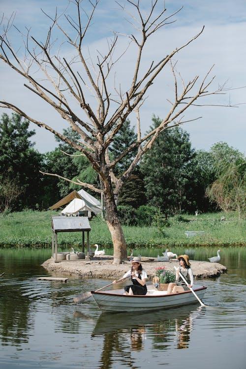 Female friends floating on boat on pond near coast