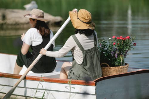 Unrecognizable female friends floating on lake in boat with basket