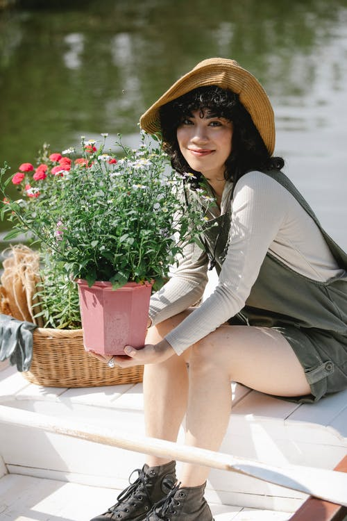 Smiling young Asian woman in overall and hat sitting in boat near wicker basket and potted flowers in pond in countryside in sunny summer day and looking at camera
